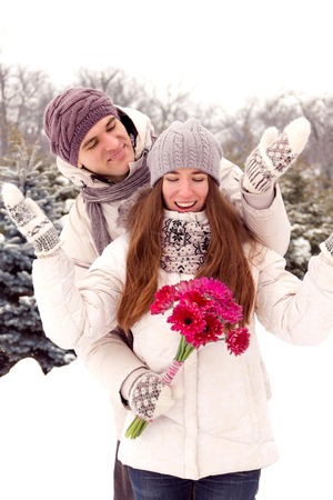 romantic flowers: Joyful young romantic couple smiling in park in winter