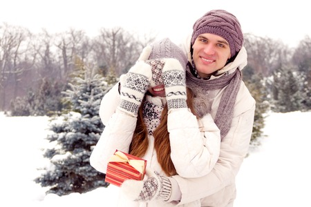 femme romantique: Joyful young romantic couple smiling in park in winter. Romantic surprise.