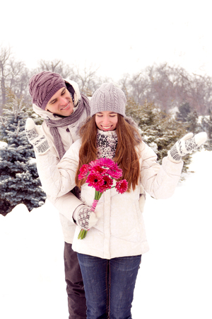 romantic man: Joyful young romantic couple smiling in park in winter