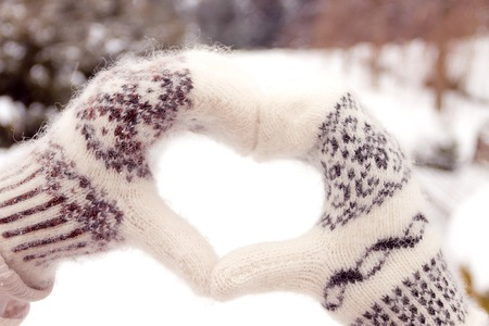romantic man: Couple in love making heart shape from hands in winter