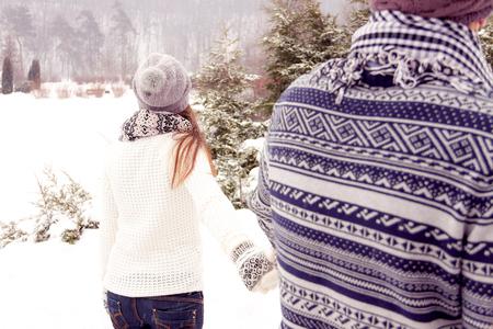 femme romantique: couple adulte jeune marchant dans la neige couverte parc