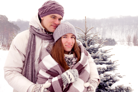 boy romantic: Beauty adult couple warming with blanket in park in winter