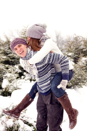girl bonding: Happy couple in love in white outerwear fool around in park in winter