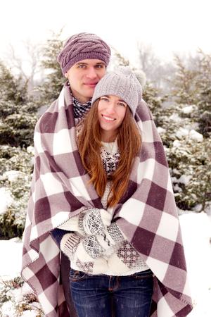 donna innamorata: coppie di bellezza adulta riscaldamento con coperta in parco in inverno