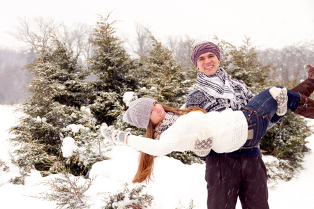 young love: Happy couple in love in white outerwear fool around in park in winter