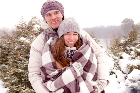 parejas romanticas: Beauty adult couple warming with blanket in park in winter