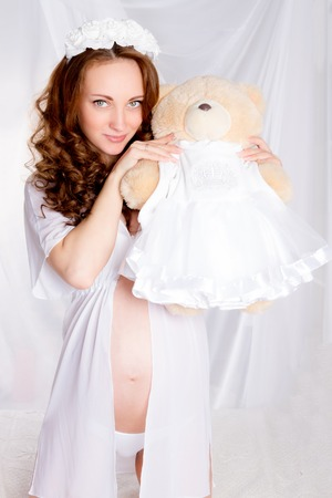 white underwear: Beautiful young pregnant woman  teenager in white underwear with teddy bear