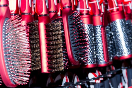 esthetics: Row of new red hairbrushes. Hairdressing salon.