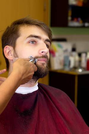 new look: Young man in hair cutting salon. Mustache. New look