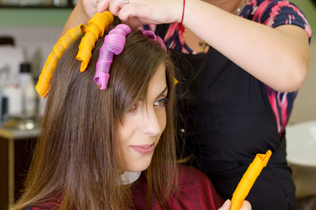 hair curlers: Young girl in hair dressing salon. Close up view. Hair curlers Stock Photo