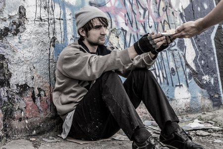Homeless man is sitting near the wall and pray for food