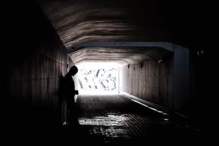 cry for help: Homeless man stand in dark tunnel and cry for eat