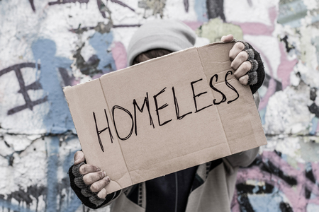 Homeless man hold in his hands an empty carton piece and pray for home Stockfoto