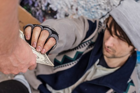 pauper: Homeless young man is taking a dollar sign laying on the ground Stock Photo