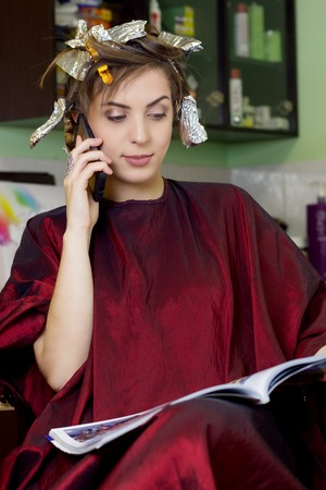 fashion magazine: Young girl in hair dressing salon is  reading fashion magazine and speaks on phone