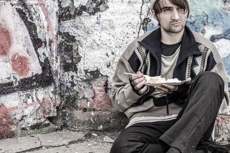 dole: Homeless young man is sitting on the ground near the wall with plate of food