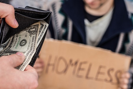 Someone is giving e few dollars to homeless man