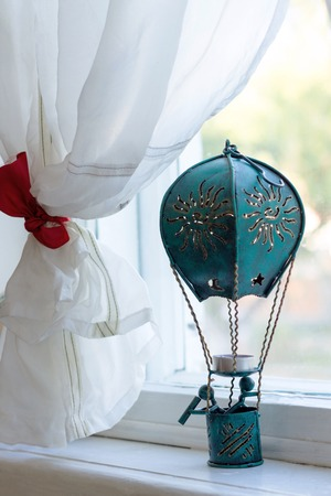 window sill: Dark blue toy air balloon is standing on white window sill Stock Photo