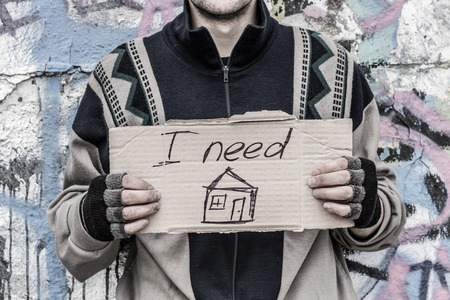 man holding sign: Homeless man holding sign asking for home