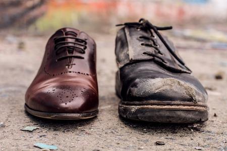 Disparo conceptual de los zapatos. Viejos zapatos gastados en comparación con los nuevos y caros.