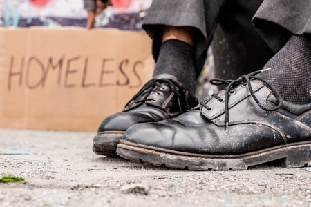 Body parts. Homeless man sitting on the street near the sign Stock Photo