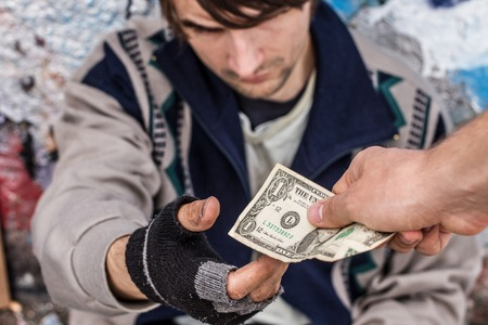 Getting help. Homeless man being handed money by volunteer