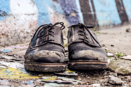 Conceptual shooting of homeless man dirty shoes left on the street Stock Photo