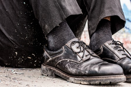 unrecognizable: Body parts. Conceptual shooting of homeless man dirty shoes