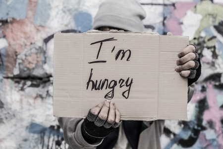 man holding sign: Homeless man holding sign asking for food