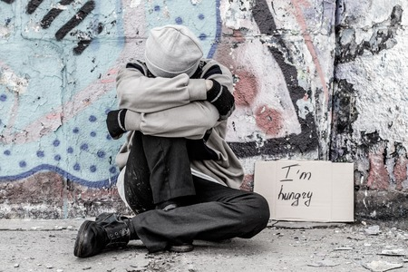 Homeless man sitting on the street with sign Im hungry Stock Photo