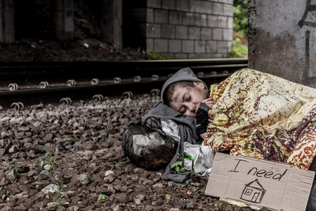 rail track: Homeless woman with sign I need home sleeping near the rail track Stock Photo