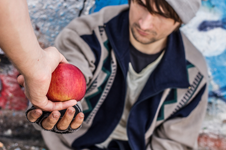 Young homeless man being handed apple by stranger