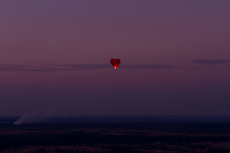 heartshaped: Heart shaped air balloon flying over amazing landscape at sunset