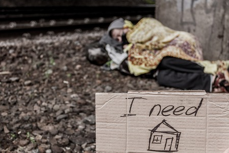 rail track: Homeless woman sleeping near the rail track with a sign asking for home in the foreground