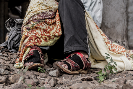 Homeless woman sitting on the street wearing sandals and torn socks