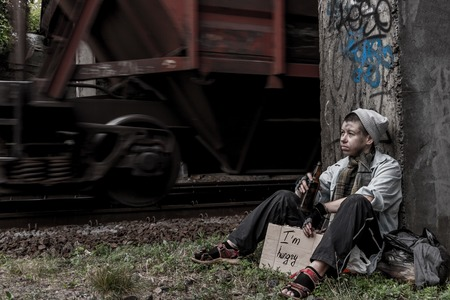 near beer: Homeless woman with sign drinking beer sitting near the rail track while the train passing