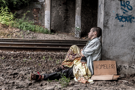 rail track: Poor homeless woman with sign sitting on the street near the rail track Stock Photo