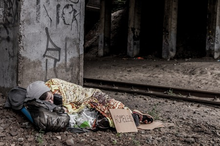 rail track: Homeless woman with sign sleeping under the bridge near the rail track