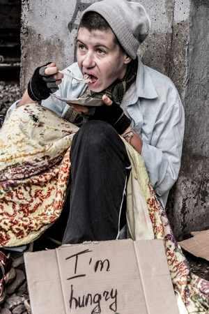 rail track: Homeless woman sitting near the rail track having meal