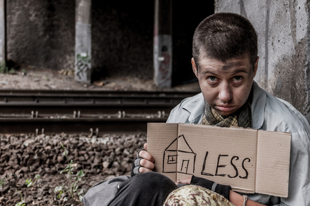 Portrait of homeless young woman with sign