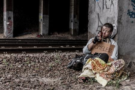 Sin hogar cerveza joven mujer beber sentado cerca de la vía férrea Foto de archivo