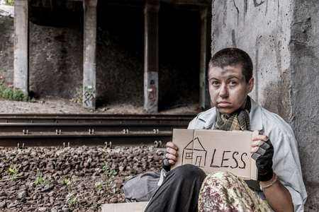 rail track: Homeless woman sitting near the rail track holding sign