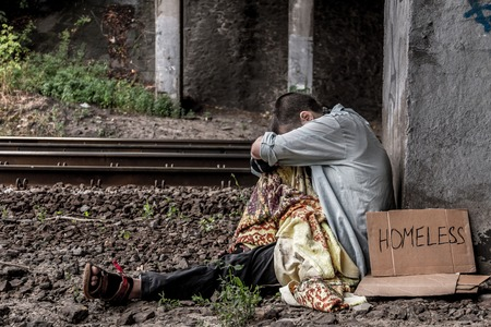 Poor homeless woman with sign sitting on the street near the rail track Stockfoto