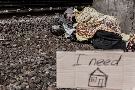 rail track: Homeless woman sleeping near the rail track with sign I need home in the foreground