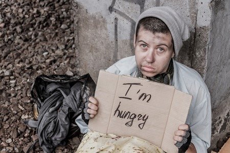 vagrant: Homeless woman holding sign asking for food