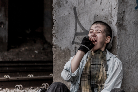 rail track: Homeless young woman siiting near the rail track and yawning Stock Photo