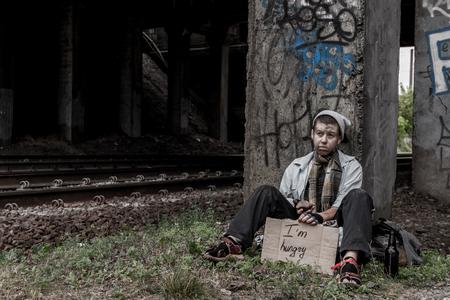 Homeless junge Frau unter der Brücke mit Zeichen sitzen für Essen zu fragen