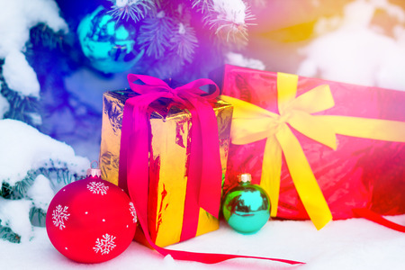 Close up shooting of two presents wraped up in colorful paper lying under the christmas tree