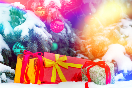 Close up shooting of several presents wraped up in colorful paper lying under the christmas tree decorated with balls