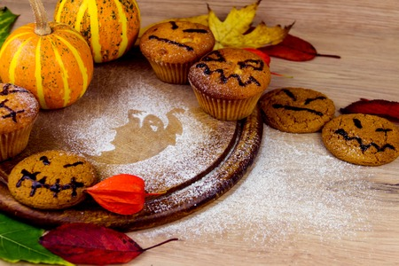 terrifying: Spooky cupcakes, pumpkin, leaves and silhouette of bat on wooden dishes Stock Photo